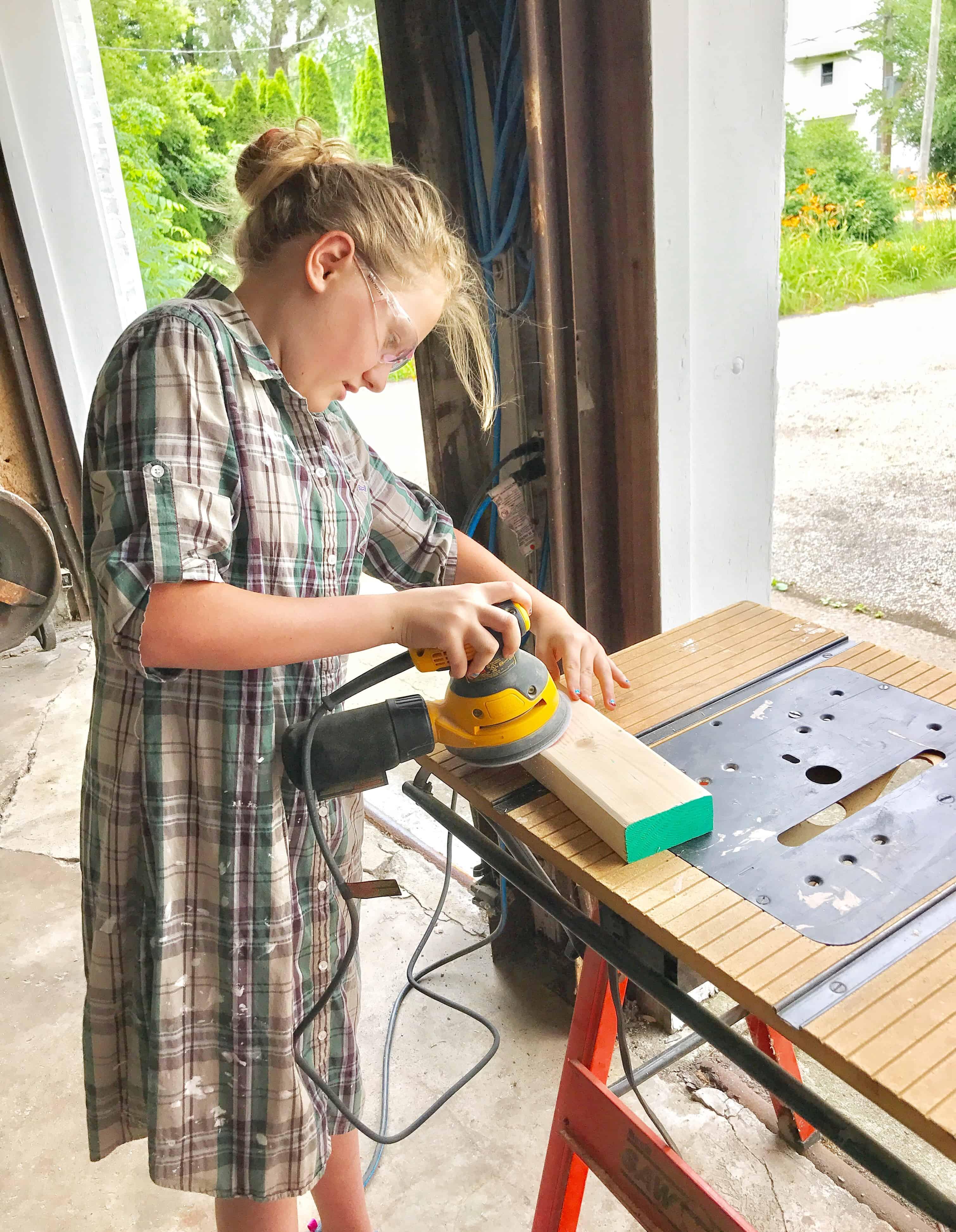 young girl sanding pieces of a diy giant Jenga