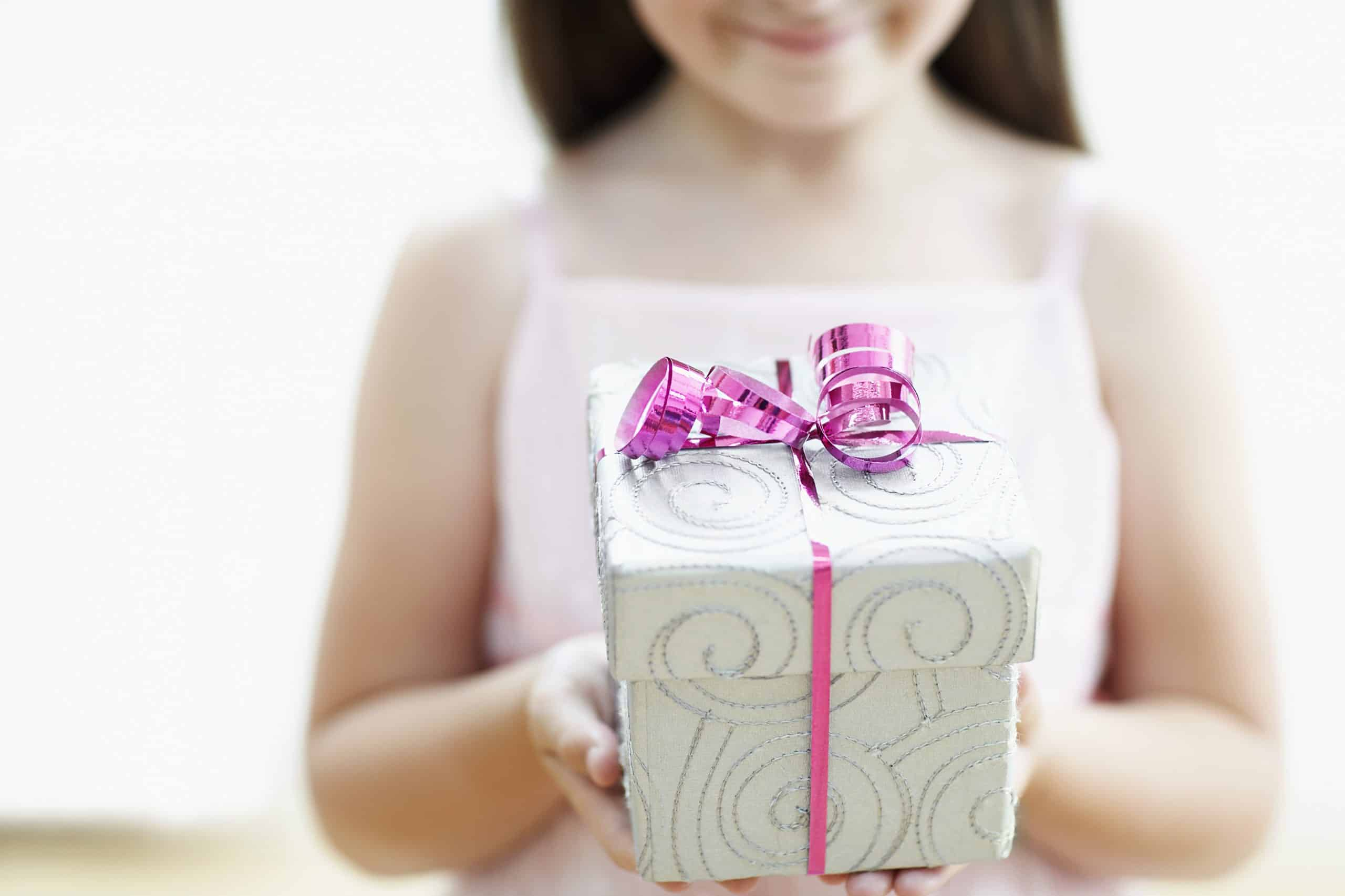 a young girl holding out a gift