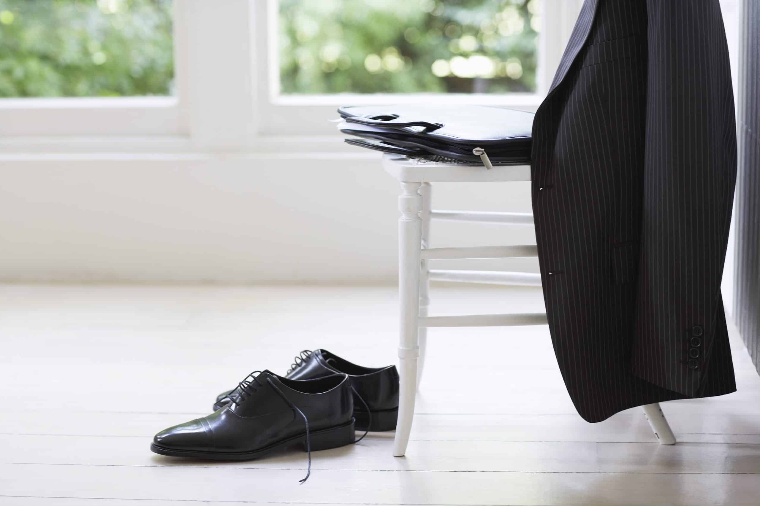 jacket on the back of a chair with empty shoes on the floor