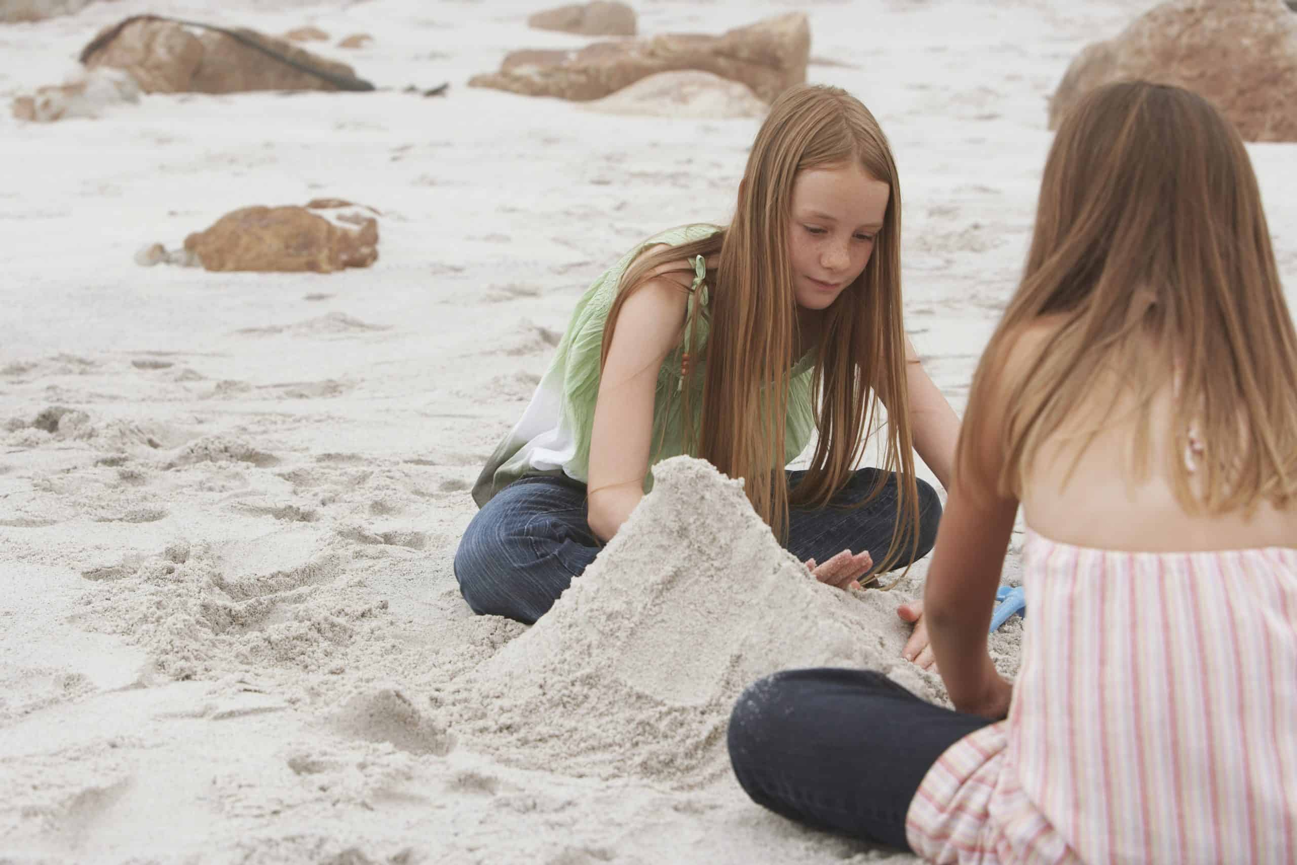 two young teens playing in the sand