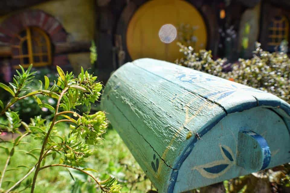 A mailbox in front of a hobbit house in Hobbiton