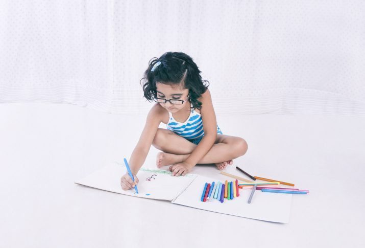 little girl drawing on the floor