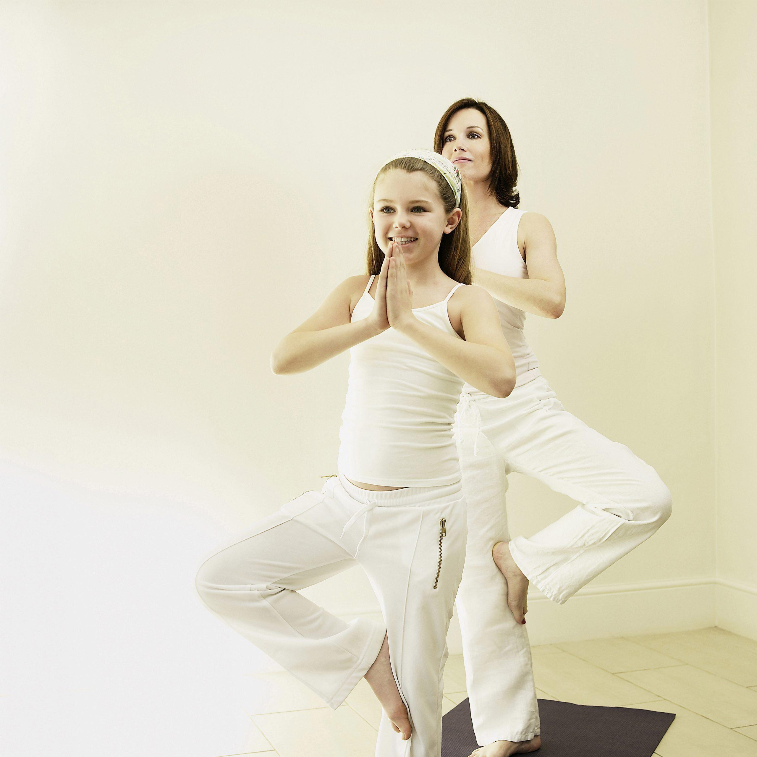woman and daughter doing yoga