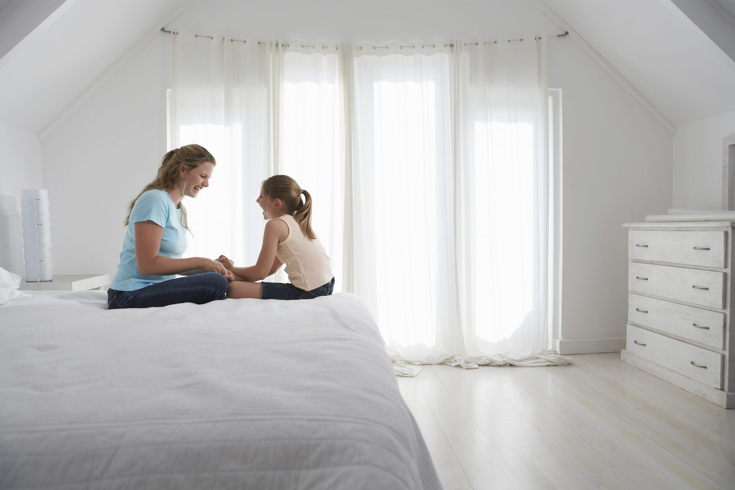 Mother and Daughter Sitting on Bed
