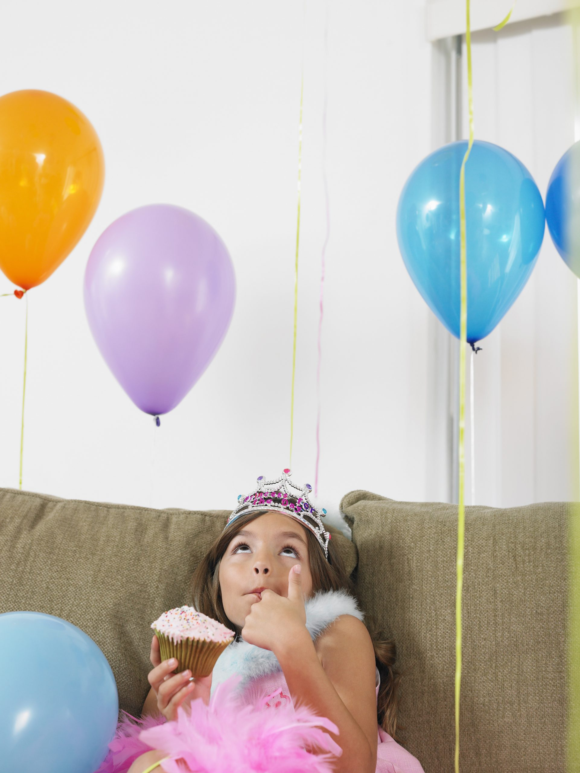 girl with balloons and cupcake