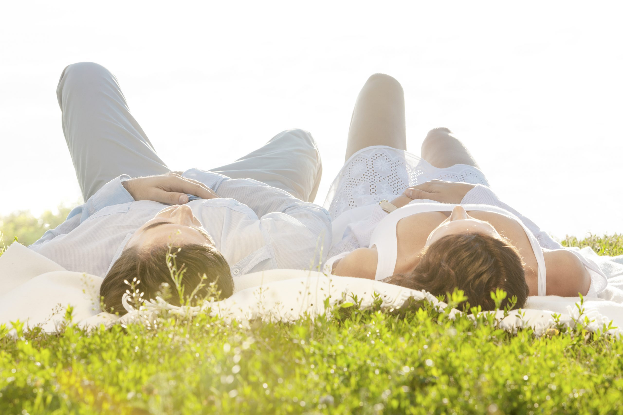 Young couple lying on picnic blanket in park